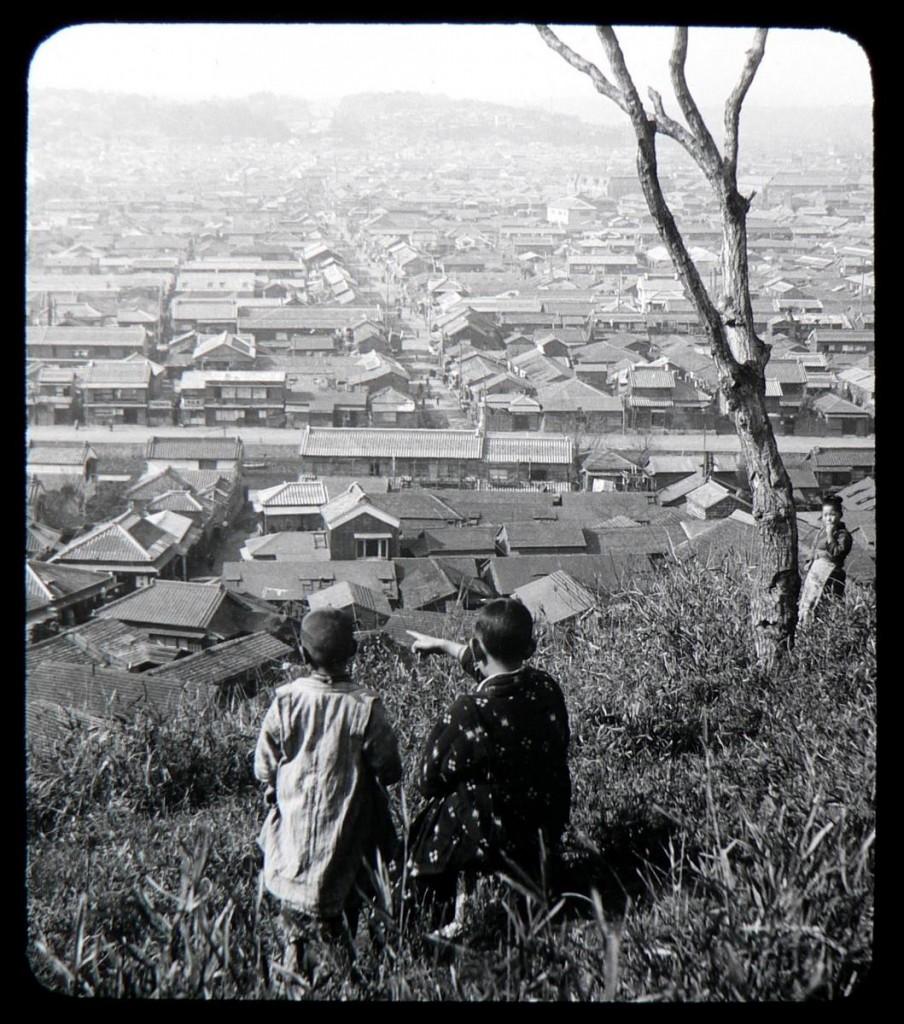 Chavales ante una panorámica de Yokohama. T. Enami, ca.1897-1900.